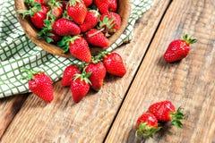 Органическая свежая зрелая клубника на старом винтажном деревянном столе Льют ягоды от деревянного шара на предпосылке Стоковое Изображение