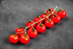 Органические зрелые свежие томаты вишни на длинной ветви на черной предпосылке текстуры Здоровая еда vegan Стоковое Изображение RF