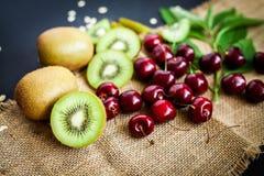 Органические киви & плодоовощ вишни на черной предпосылке Стоковые Фото