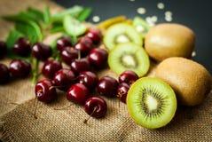 Органические киви & плодоовощ вишни на черной предпосылке Стоковые Изображения RF