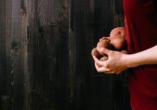 органические овощи Руки держа свежие картошки Черная деревянная предпосылка с космосом экземпляра стоковые фото