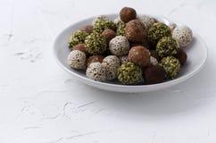 Органические укусы энергии с датами, семенами тыквы, миндалиной, грецким орехом и сезамом на белой предпосылке стоковые изображения