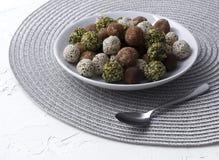 Органические укусы энергии с датами, семенами тыквы, миндалиной, грецким орехом и сезамом на белой предпосылке стоковое изображение