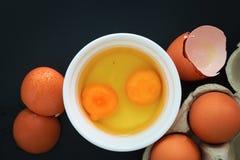 Органические яичка и желток сломанные в белой чашке стоковые изображения