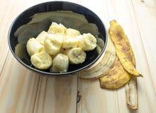 Органический банан в черном шаре с корками на деревянной предпосылке Стоковые Фото
