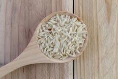 Органический коричневый рис в деревянной ложке на деревянной предпосылке Стоковые Изображения RF