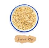 Органический коричневый рис в чашке с биркой имени на белой предпосылке Стоковые Фото