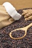 Органический коричневый рис разливая из мешка Стоковые Фото