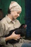 Органический цыпленок удерживания фермера под его оружиями стоковые изображения rf