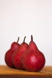 3 органических красных груши на деревянной доске Стоковые Изображения