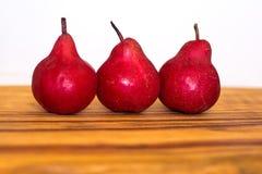 3 органических красных груши на деревянной доске Стоковое Фото