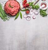 Органическое семенить мясо с варить ингридиенты, деревянную ложку и миномет специй на серой каменной предпосылке, взгляд сверху Стоковые Изображения