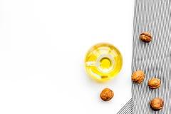 Ореховое масло для заботы или варить кожи Масло грецкого ореха в опарнике около грецкого ореха в шаре на белом космосе экземпляра Стоковые Фото