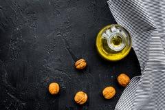 Ореховое масло для заботы или варить кожи Масло грецкого ореха в опарнике около грецкого ореха в шаре на черном космосе экземпляр Стоковая Фотография