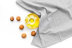 Ореховое масло для заботы или варить кожи Масло грецкого ореха в опарнике около грецкого ореха в шаре на белом взгляд сверху пред Стоковые Фото