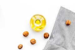 Ореховое масло для заботы или варить кожи Масло грецкого ореха в опарнике около грецкого ореха в шаре на белом космосе экземпляра Стоковые Изображения