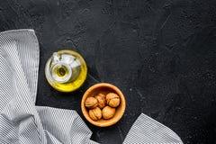 Ореховое масло для заботы или варить кожи Масло грецкого ореха в опарнике около грецкого ореха в шаре на черном космосе экземпляр Стоковые Изображения