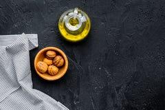Ореховое масло для заботы или варить кожи Масло грецкого ореха в опарнике около грецкого ореха в шаре на черном космосе экземпляр Стоковое Изображение