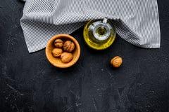 Ореховое масло для заботы или варить кожи Масло грецкого ореха в опарнике около грецкого ореха в шаре на черном космосе экземпляр Стоковое Фото