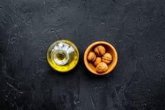 Ореховое масло для заботы или варить кожи Масло грецкого ореха в опарнике около грецкого ореха в шаре на черном космосе экземпляр Стоковые Фото