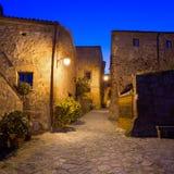 Ориентир ориентир Civita di Bagnoregio, средневековый взгляд деревни на сумерк. Италия Стоковое Изображение