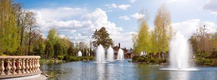 Орнаментальные сады с озером, зацветая кустами и фонтанами Знамя для вебсайта Стоковые Фотографии RF