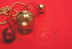 Орнаменты красных и золота рождества на красной предпосылке стоковые фото