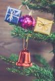 Орнаменты подарка рождества висят на рождественской елке имеют предпосылку древесины космоса Стоковая Фотография RF