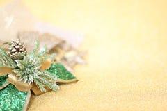 Орнаменты рождества на предпосылке освещения яркого блеска золота Стоковые Фото