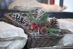 Орнаменты рождества красные, снежный украшенный centerpiece таблицы конуса сосны Предпосылка рождества с расположением в плетеной Стоковые Фотографии RF