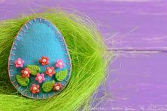 Орнамент пасхального яйца с красочными пластичными шариками цветков и листьев Орнамент яичка войлока в гнезде и на деревянной пре Стоковые Фото