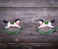 Орнамент рождества декоративный - 2 деревянных лошади на деревянной задней части Стоковое фото RF