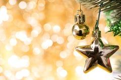 Орнамент рождества украшает на ели с bokeh золота Стоковые Изображения