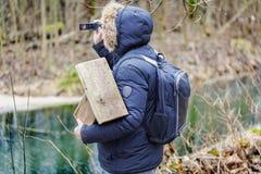 Орнитолог с клеткой камкордера и птицы в парке около реки Стоковые Фотографии RF