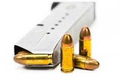 Оружие и пули положили дальше белый пол стоковая фотография