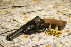 Оружие с пулями клало вниз на запачканные доллары стоковое изображение
