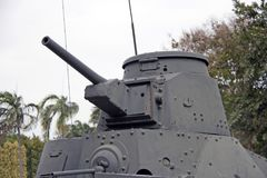 Оружие танка на зеленом дереве и белой предпосылке неба Оно на танке стоковые фотографии rf