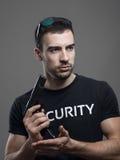 Оружие уверенно грубого мачо охранника перезаряжая смотря прочь Стоковое Фото
