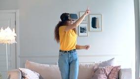 Оружия движения молодой женщины, пока носящ оборудование VR видеоматериал