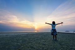 Оружия женщины стоящие протягиванные на заходе солнца Стоковое фото RF