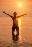 Оружия женщины фитнеса открытые к заходу солнца восхода солнца Стоковые Изображения