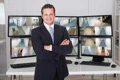 Оружия менеджера стоящие пересеченные против мониторов на офисе Стоковое фото RF