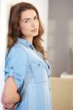 Оружия молодой женщины стоящие за усмехаться стоковое фото