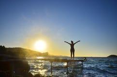 Оружия счастливой женщины стоящие протягиванные назад и наслаждаются жизнью на пристани пляжа на заходе солнца Стоковая Фотография RF