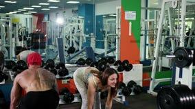 Оружия человека и женщины изгибая одновременно путем поднимаясь гантели, разминка в спортзале видеоматериал