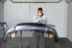 Оружи брызга пользы художников для того чтобы приложить краску к бамперу Стоковое Изображение RF