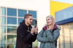 Осадка Гая показывает девушку сломленного телефона ревя Стоковые Фото