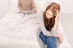 Осадка девушки сидит на краю кровати и парень от заднего сидит за концом-вверх компьтер-книжки Стоковые Фотографии RF