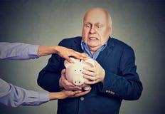 Осадка пожилых людей вспугнула бизнесмена держа копилку пробуя защитить его сбережения от быть украденным Стоковое Фото