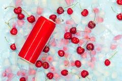 Освежающий напиток в консервной банке металла против предпосылки прозрачных и розовых кубов льда со зрелыми ягодами сладкой вишни стоковые изображения